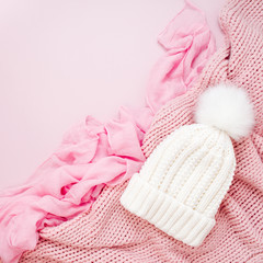 Warm winter clothes and Christmas decor. Arrangement in pastel pink colors.
