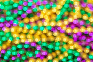 Out of focus background of shiny and colorful Mardi Gras beads