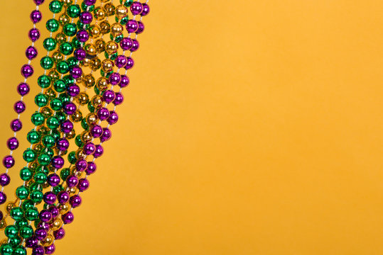 Mardi Gras beads against golden yellow background with copy space