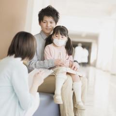 病院の待合室で順番を待つ親子と問診をする看護師