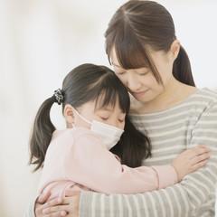 病気の娘を抱き締める母親