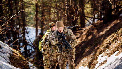 team of special forces weapons in cold forest. Winter warfare and military concept