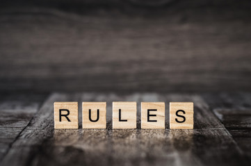 the word rules made of bright wood cubes with black letters on a dark wooden background