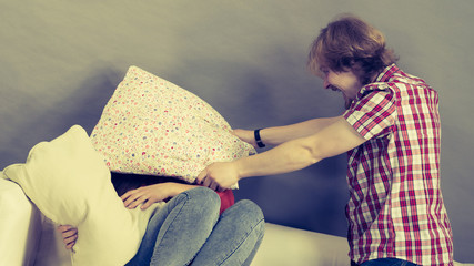 Man and woman having pillow fight.