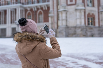 Young woman tourist shoots video on a smartphone in the winter