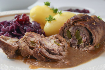 beef roulade with red cabbage, potatoes and sauce, german meat roll stuffed with cucumbers and bacon,  close up