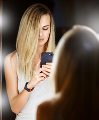 the girl makes selfie in the mirror. considering yourself in the phone screen