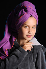 Close-up portrait of a beautiful adorable pretty young teen girl with a towel on her head and in a bathrobe. The child after bathing.