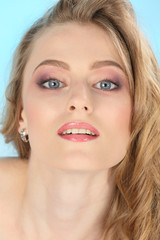 Close-up portrait of a young attractive adult girl with blond hair, big beautiful eyes and bright make-up.