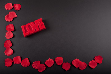 Black board with love word and rose petals