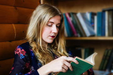 Young pretty vintage stylish student girl reading poetry book