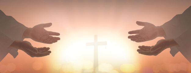 Resurrection of Easter Sunday concept: Silhouette two humans open spiritual hands over blurred cross sunset background.