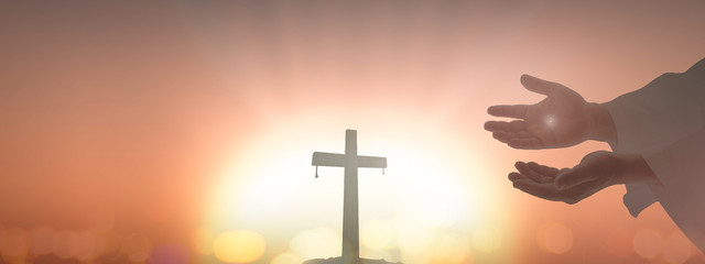 Ascension day concept: Jesus Christ hands showing scars over blurred cross sunset background.
