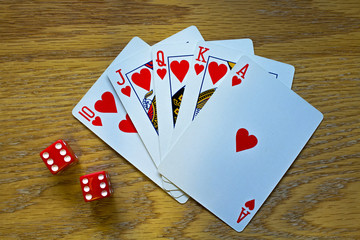 Closeup of Five Playing Cards - a Royal Flush - and two die