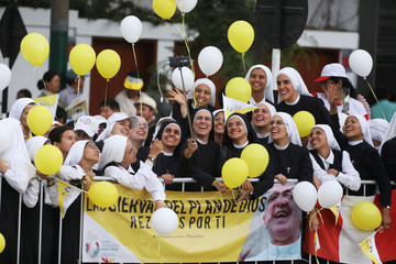 Nuns take a selfie while waiting for Pope Francis to drive past, in Lima