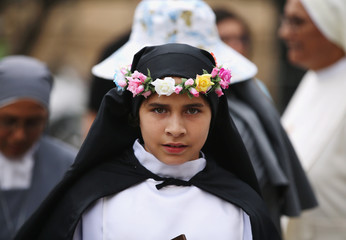 A young woman dressed as St Rosa of Lima, patron saint of Peru, waits for Pope Francis to arrive at the nunciature, in Lima