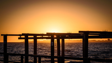 The sun sets over the horizon of Port Phillip Bay with a silhouetted wooden boat launch structure in the foreground. Melbourne Australia