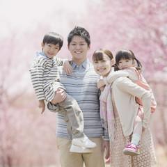 桜の前で微笑む家族