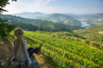 Vineyards on a hills. Young woman with blond dreadlocks on the edge of a cliff and looks down at on the Douro Valley, Portugal.