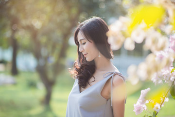 Portrait of beautiful asian woman  outdoors in a forest. Pretty Thai girl with flower.