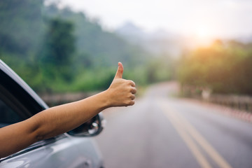 Hand of woman traveler with thumbs up from car form the asphalt road go to travel.