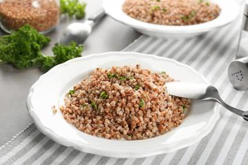 Plate of tasty buckwheat porridge on table
