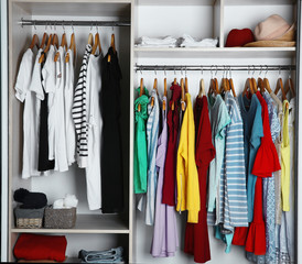 Wardrobe with many different clothes, closeup