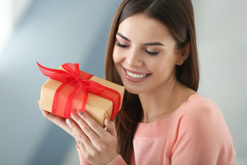 Beautiful young woman holding gift box at home