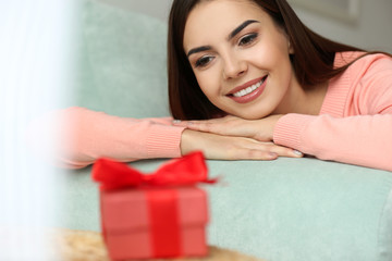 Beautiful young woman looking at gift box, closeup