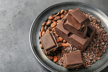 Plate with chocolate and cocoa products on table