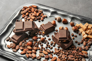 Tray with chocolate, hazelnuts, cocoa and coffee beans on table