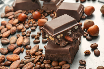 Pieces of chocolate, hazelnuts, cocoa and coffee beans on metal tray, closeup
