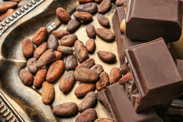 Pieces of chocolate and cocoa beans on metal tray, closeup