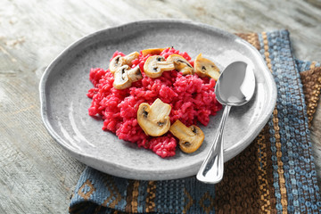 Plate of tasty beetroot risotto with mushrooms on table, closeup