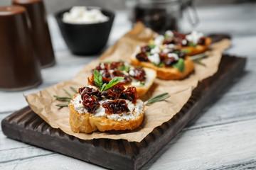 Tasty bruschettas with sun-dried tomatoes on wooden board, closeup
