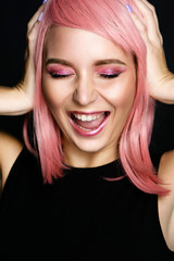 Girl in pink wig with professional make-up laughs