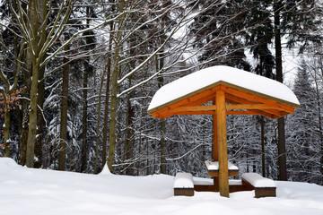 Snowy bench in winter landscape. National park Sumava in Czech Republic.