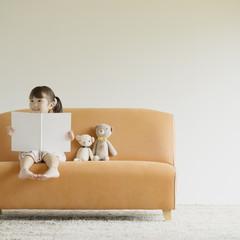 ソファーに座り絵本を読む女の子