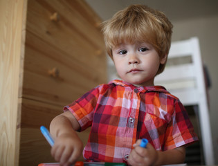 Small boy child drawing with colorful marker pen.