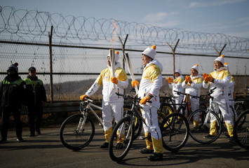 Torchbearers poses for photographs as they participate in the Olympic torch relay on the Grand Unification Bridge which leads to the truce village Panmunjom, just south of the demilitarized zone separating the two Koreas, in Paju