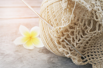 light brown unfinished  doily and  crochet hook on old wooden desk, closeup