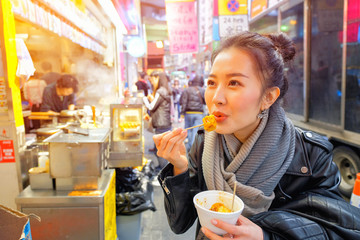 Asian young woman eating Chinese Steamed Dumpling on a street in Hong Kong Fototapete