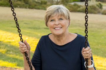 happy portrait of American senior mature beautiful woman on her 70s sitting on park swing outdoors relaxed smiling and having fun in healthy aging
