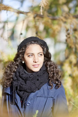 Portrait of young woman with curly hair on sunny day