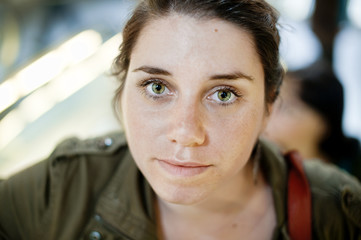 Headshot of young serious woman looking at camera