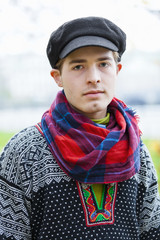 Portrait of young man in flat cap and checked scarf looking at camera
