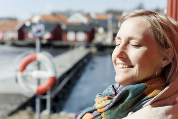 Adult woman standing in harbor with closed eyes smiling