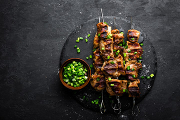 Grilled meat skewers, shish kebab on black background, top view