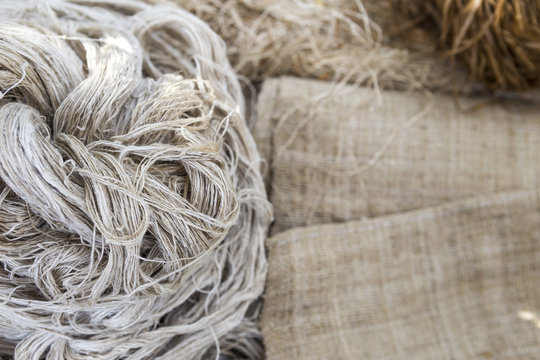 Natural color threat on blurred hessian fabric, natural material concept