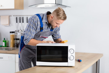 Male Technician Checking Microwave